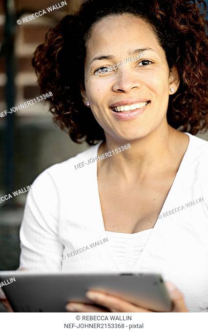 Woman holding digital tablet, looking at camera