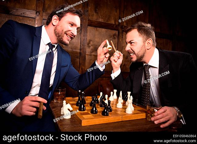 Rich businessmen playing chess demonstrating rivalry or competition. Two executive men have competition between their enterprises, companies, firms