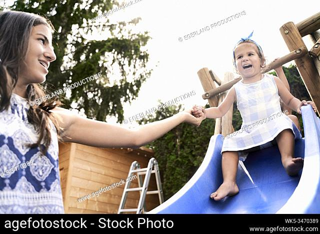 Young girl helps her little sister going down the slide
