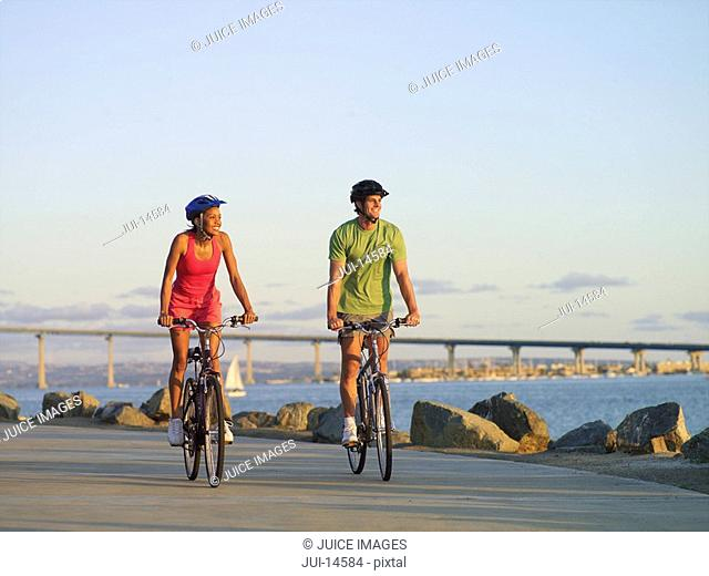 Young couple cycling on boulevard by sea at sunset, smiling