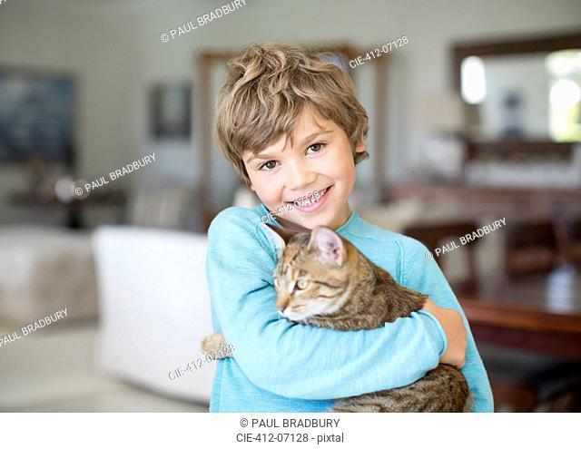 Boy hugging cat in living room
