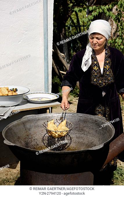 Kazakh woman draining oil from deep fried dough outdoors in Shymkent Kazakhstan