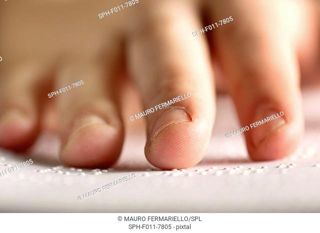 Fingers touching braille, close up