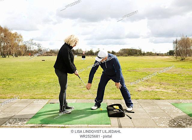 Man teaching golf to woman at driving range