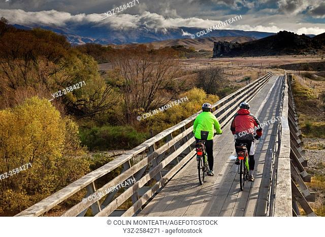 Cyclists crossing bridge, Otago Rail Trail, Otago, New Zealand