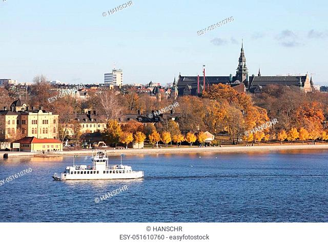 The beautiful Skeppsholmen and a ferry in central Stockholm during the autumn. Sea, houses and trees