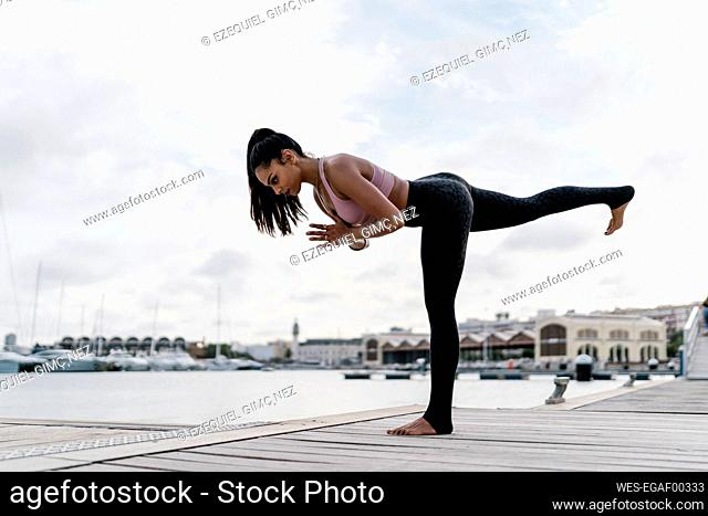 Female athlete practicing warrior 3 pose on pier at harbor against sky