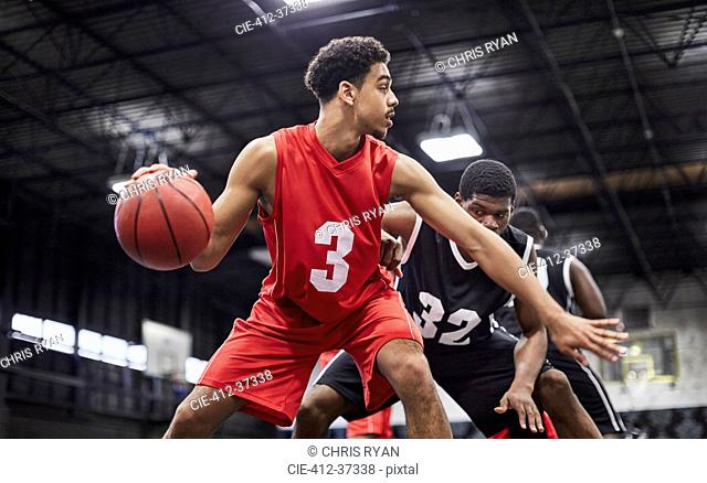 Young male basketball player dribbling the ball, playing game in gymnasium