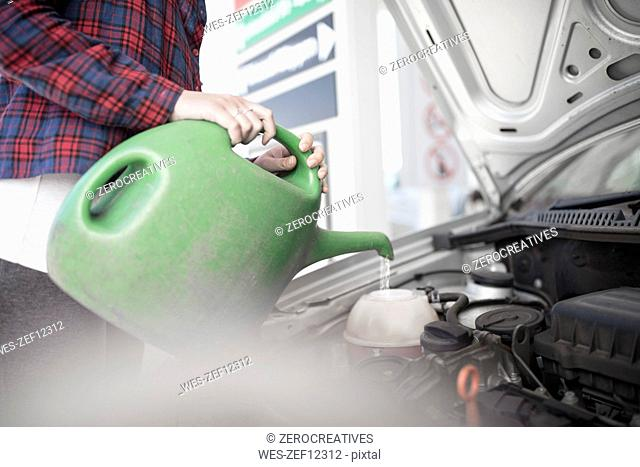 Woman filling up car with water canister