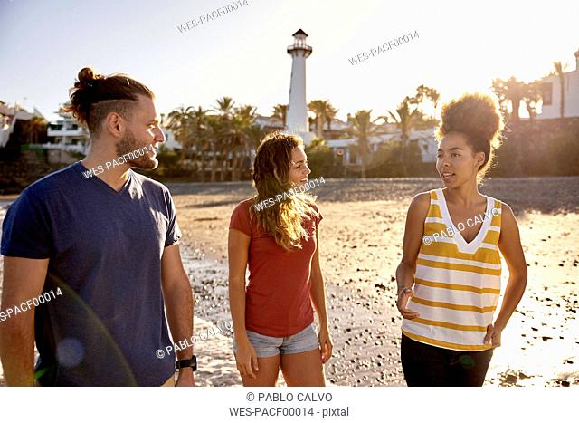 Spain, Canary Islands, Gran Canaria, three friends strolling on the beach at evening twilight