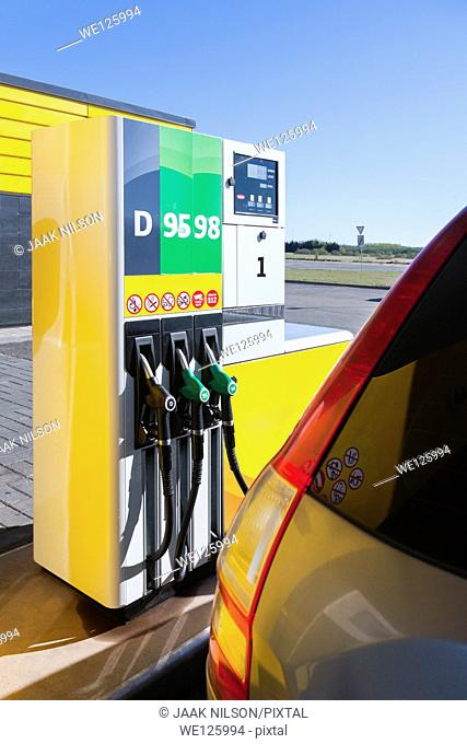 Car in gas station. Closeup of fueling, petrol dispenser and nozzles. Back side view of car with tail lights. Estonia