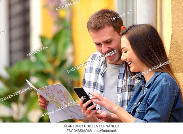 Happy couple of tourists checking smart phone and map searhing location in the street on vacation
