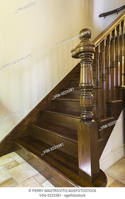Ceramic tile floor and brown stained oak wood staircase leading to the upstairs floor inside a 2006 reproduction of a 16th century Renaissance castle style...