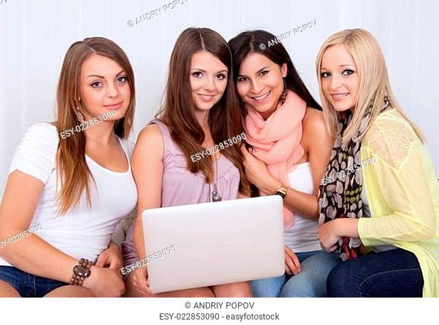 Women on a couch sharing a laptop