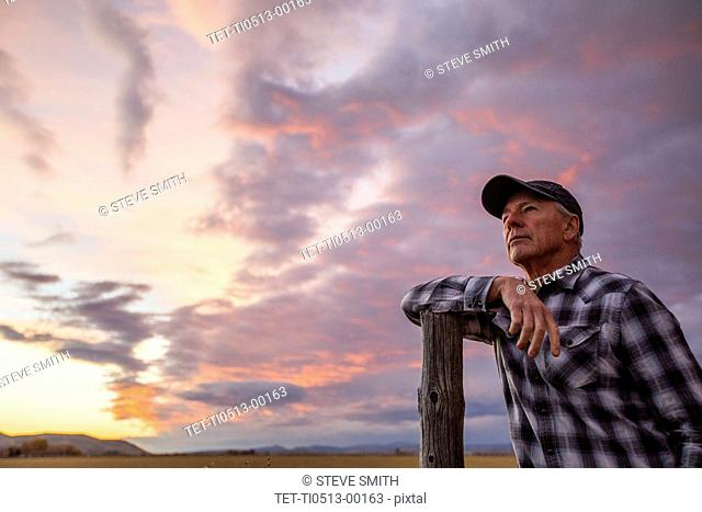 Senior man leaning on fence post at sunset