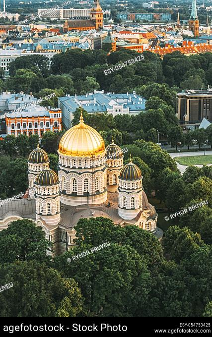 Riga, Latvia. Riga Cityscape. Top View Of Riga Nativity Of Christ Cathedral - Famous Church And Landmark In Summer Evening. Golden Yellow Domes