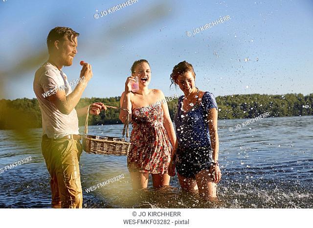 Playful friends splashing in a lake taking a drink