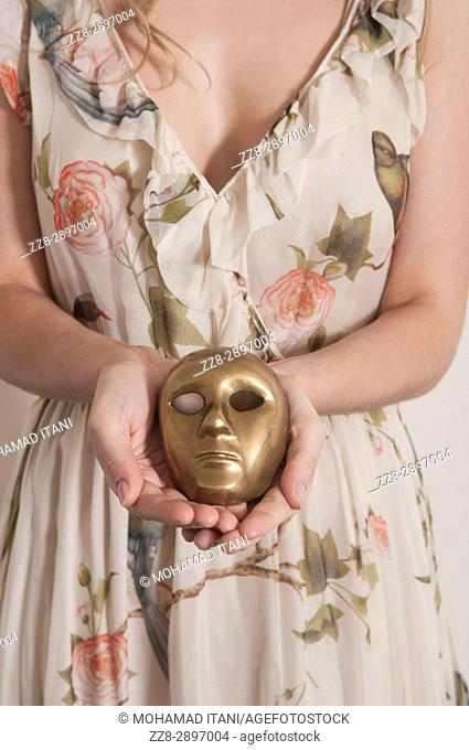 Close up of a woman holding a metal mask