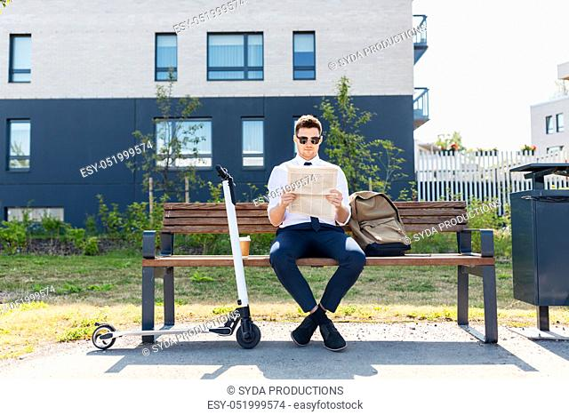 businessman with scooter reading newspaper in city