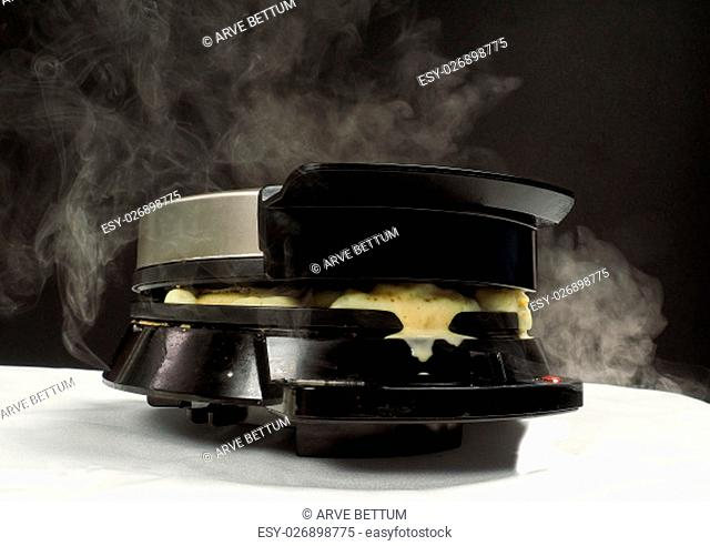 Making fresh steaming hot waffles with a waffle maker towards black on white