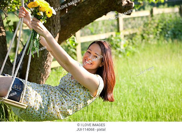 Portrait happy brunette woman swinging on tree swing with flower bouquet in sunny summer rural yard