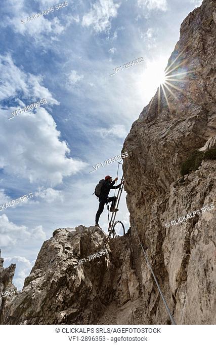 Europe, Italy, Veneto, Belluno, Sexten Dolomites. a hiker along the via ferrata of the forks in the Paterno (Paternkofel) mount
