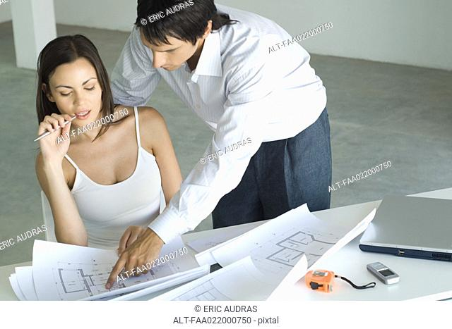 Couple looking at blueprints together, man looking over woman's shoulder, pointing to blueprint