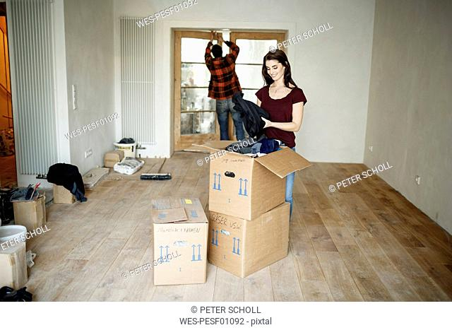 Couple moving into their new home, woman unpacking boxes