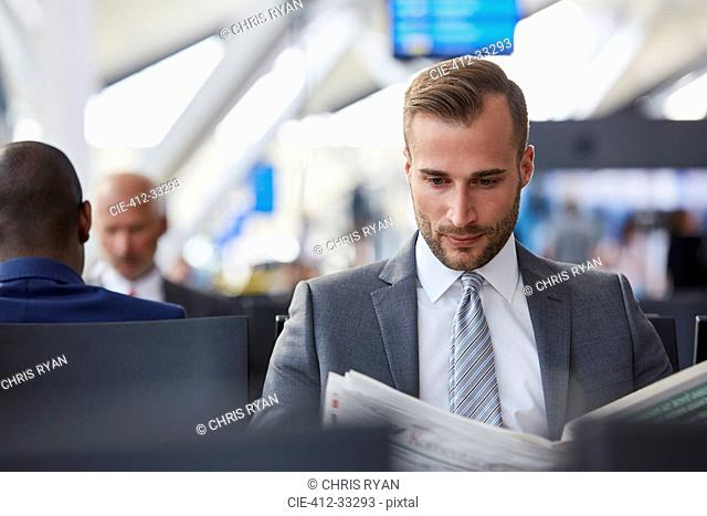 Businessman reading newspaper in airport departure area