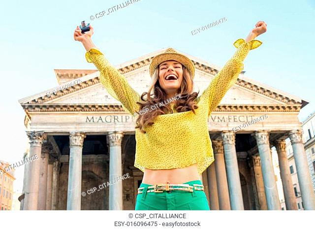 Portrait of happy young woman with photo camera rejoicing in fro