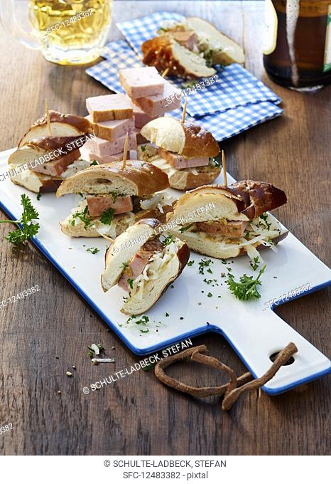 Lye bread roll snack with beef and pork meatloaf on a ceramic board