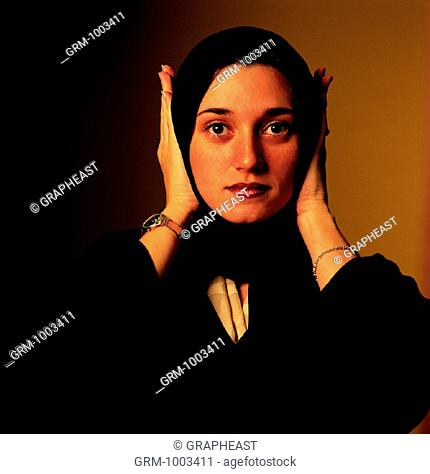 Arab woman covering her ears with her hands