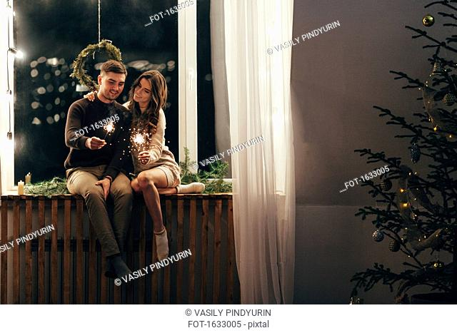 Happy couple playing with sparklers while sitting on window sill during Christmas