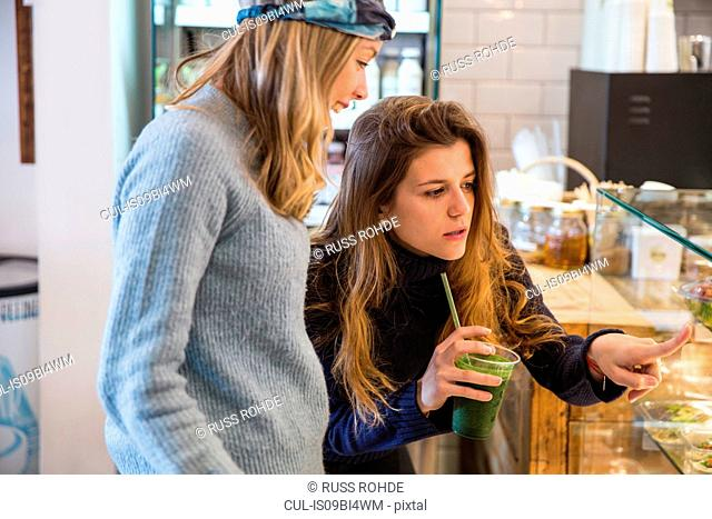 Young woman and friend looking at fresh food display cabinet in cafe