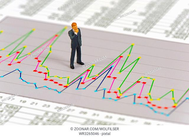 model figure of banker is thinking about charts and strategy of stock market