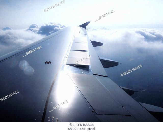 Sun shining on airplane wing flying over puffy cumulus clouds in the sky