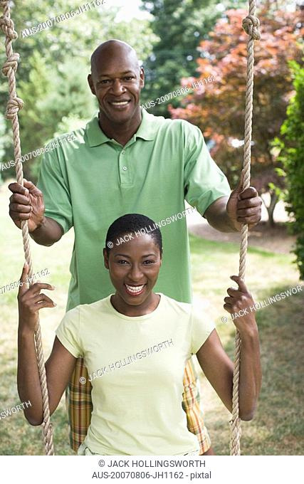 Portrait of a mid adult woman sitting on a rope swing with a mature man pushing her