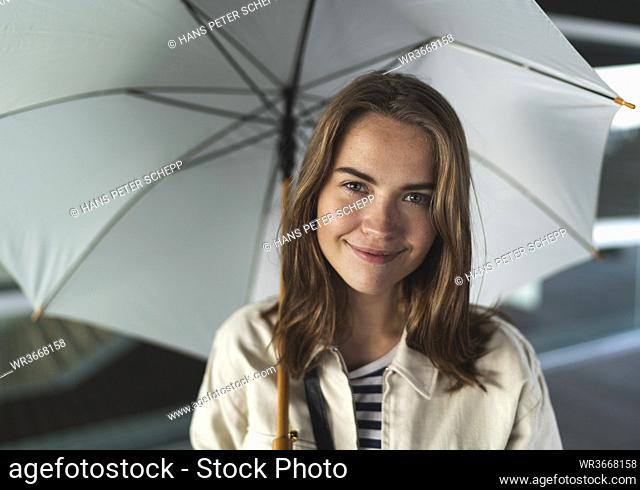Close-up of happy young woman with umbrella standing in city