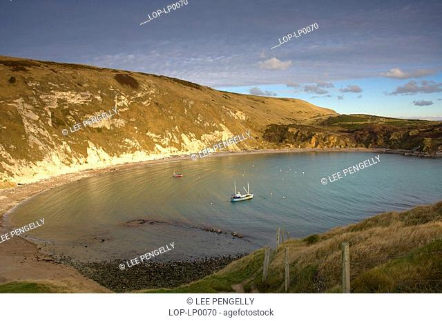 England, Dorset, Lulworth, A fishing trawler anchored in Lulworth Cove on a bright winter day