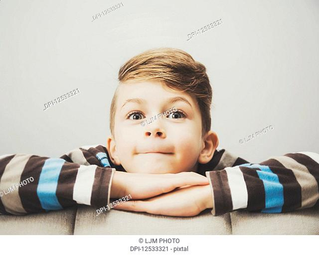 Portrait of a young boy looking from behind a couch with a contented look and with his arms folded; Langley, British Columbia, Canada