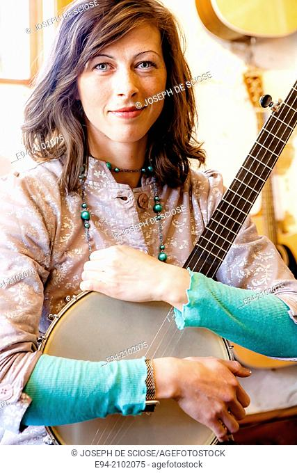 A 28 year old brunette woman holding a banjo on her lap with grinning at the camera