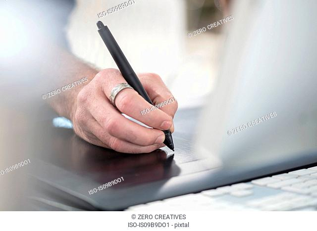 Cropped view of man writing with digital pen