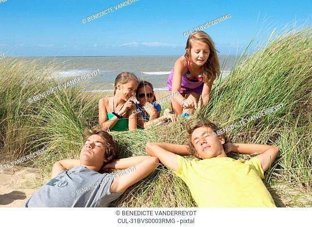 Girls teasing boys in sand dune