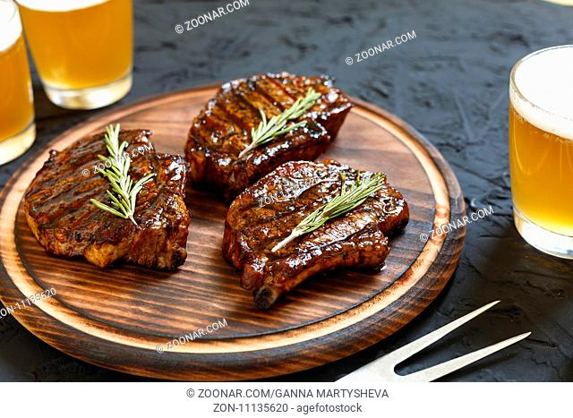 Very delicious steak BBQ and beer in glasses on a black stone background Dinner