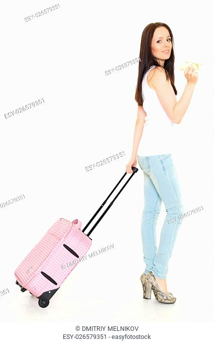 Young happy woman with suitcase and model of plane stands on a white background. Vacation