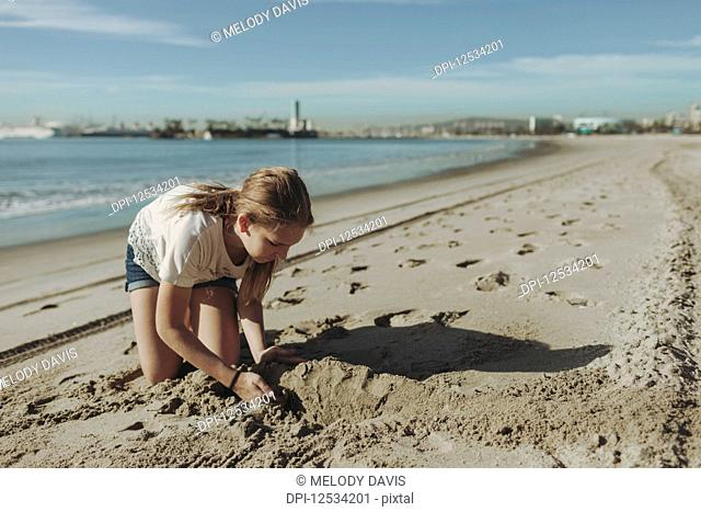 A girl playing in the sand at the beach; Long Beach, California, United States of America
