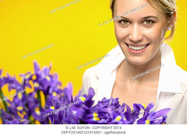 Smiling woman with spring blue flowers iris