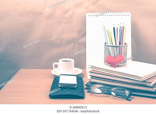 office desk: coffee with phone, wallet, calendar, color pencil box, stack of book, heart, eyeglasses on wood background vintage style