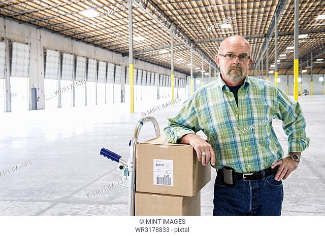 Caucasian male standing next to hand truck in front of loading dock doors inside of a new warehouse