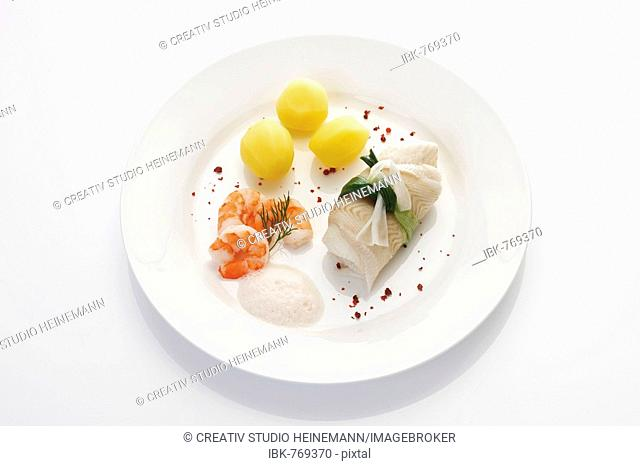 Seafood dish: rolled halibut wrapped in a leek bow with boiled potatoes, shrimp (prawns) and frothy white wine sauce